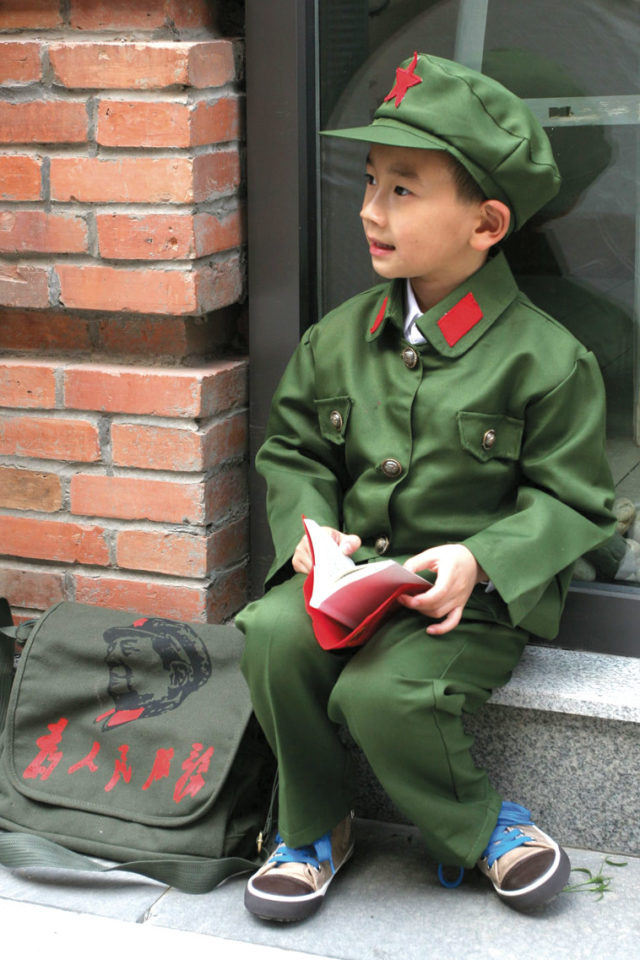 Boy in an imitation Red Army uniform with 'Serve the People' slogan printed on his bag. Source: ImagineChina