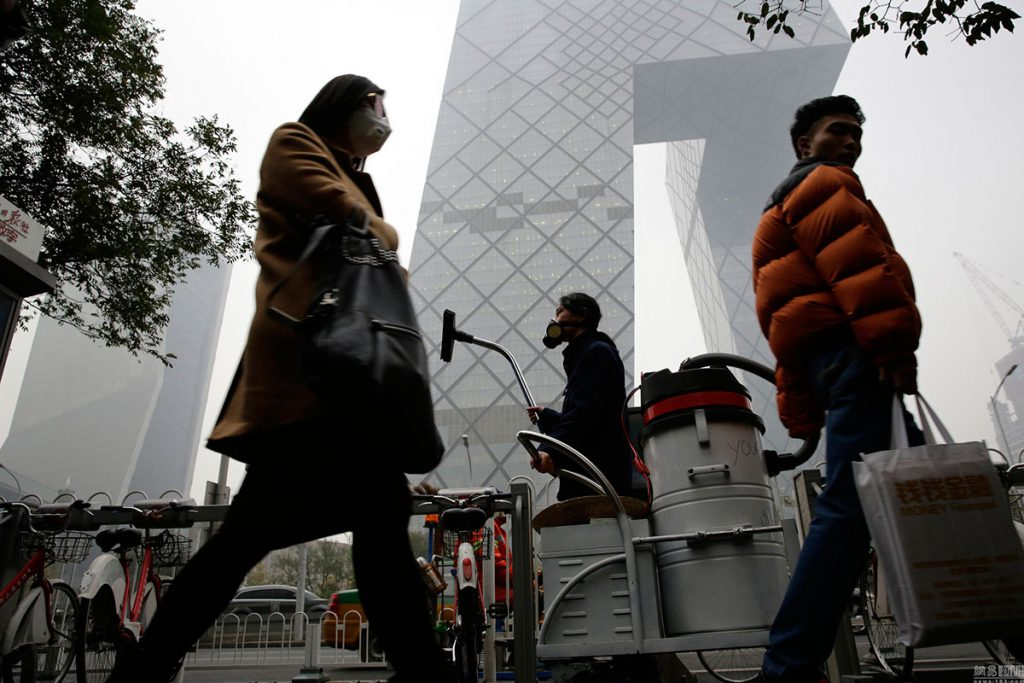 Wang Renzheng, a Chinese performance artist better known as Nut Brother, with the industrial vacuum cleaner he uses to suck up smog and turn it into 'smog bricks' Photo: tech.163.com