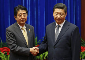 Abe and Xi shake hands at the APEC meeting in Beijing Photo: gdb.voanews.com